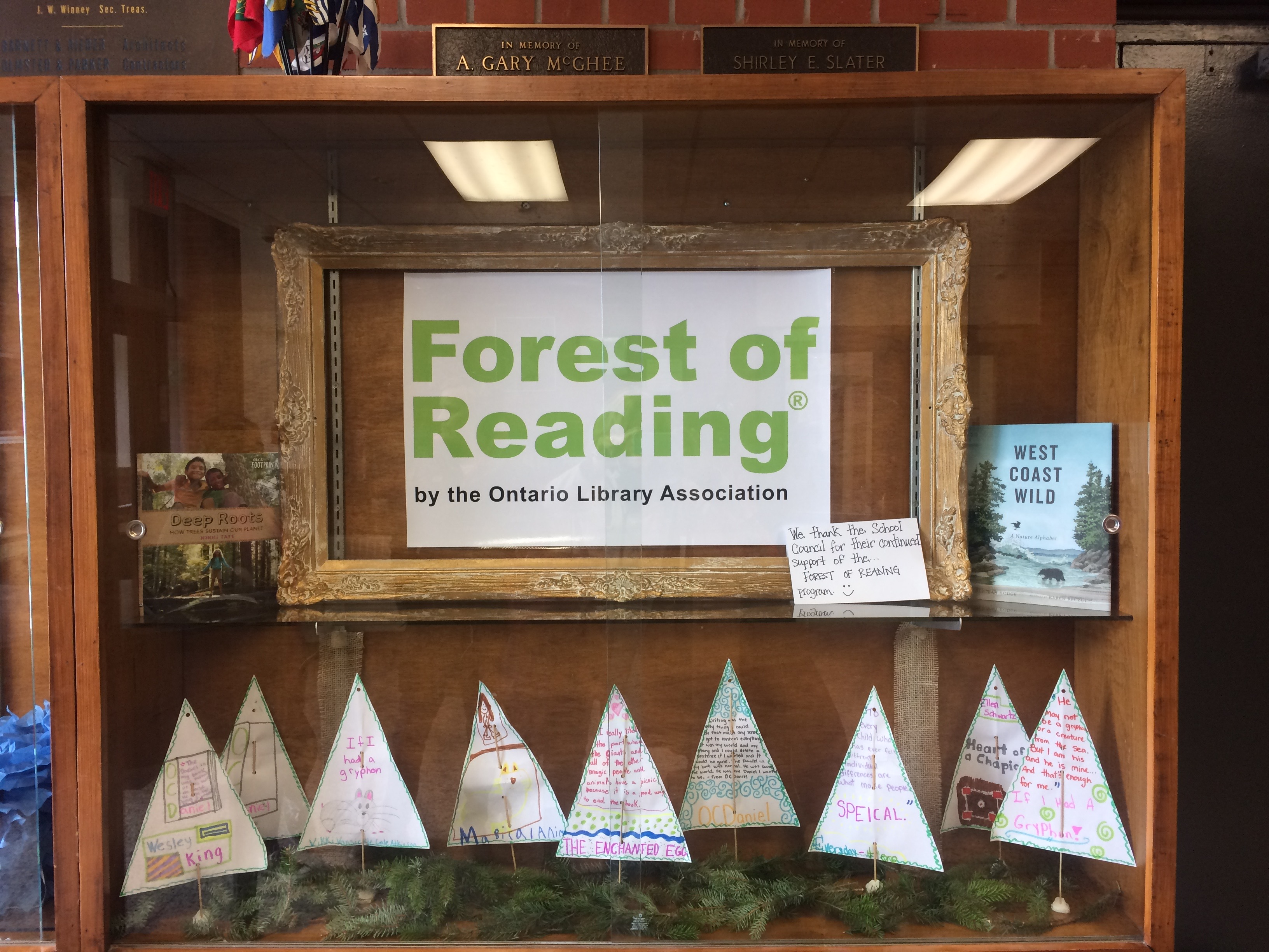 display case with Forest of Reading banner and trees