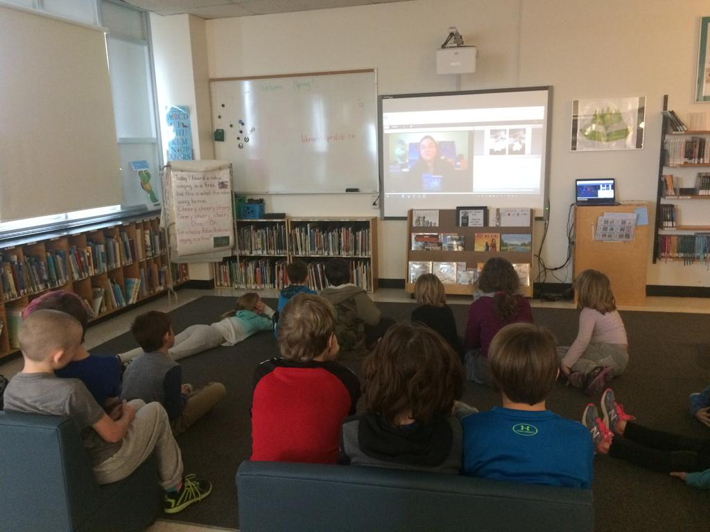 students in library watching a virtual author visit from Smartboard