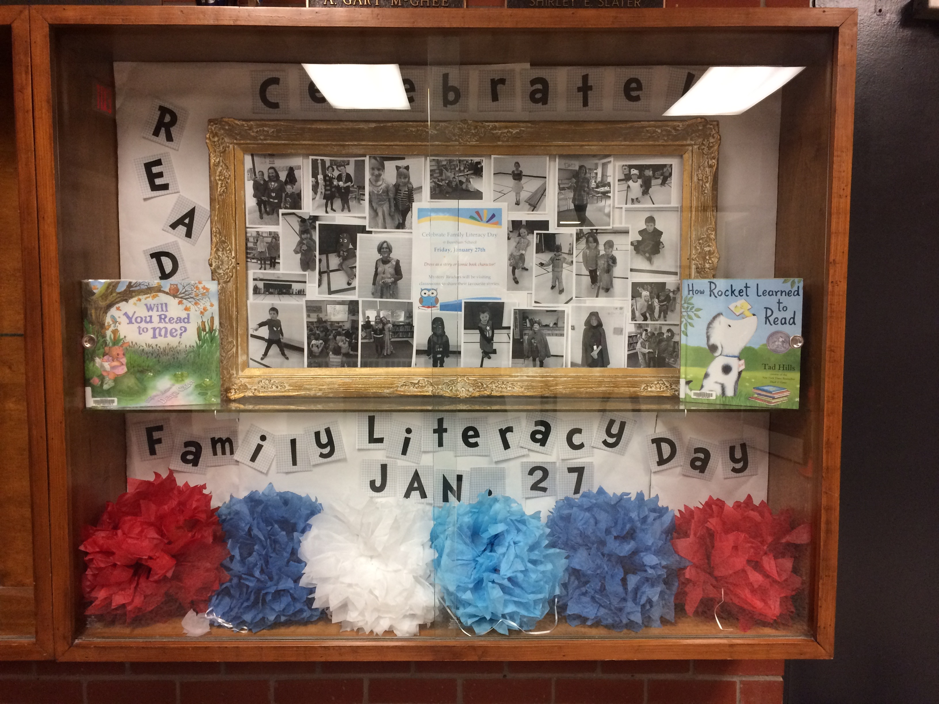 display case with Family Literacy Day pictures and books